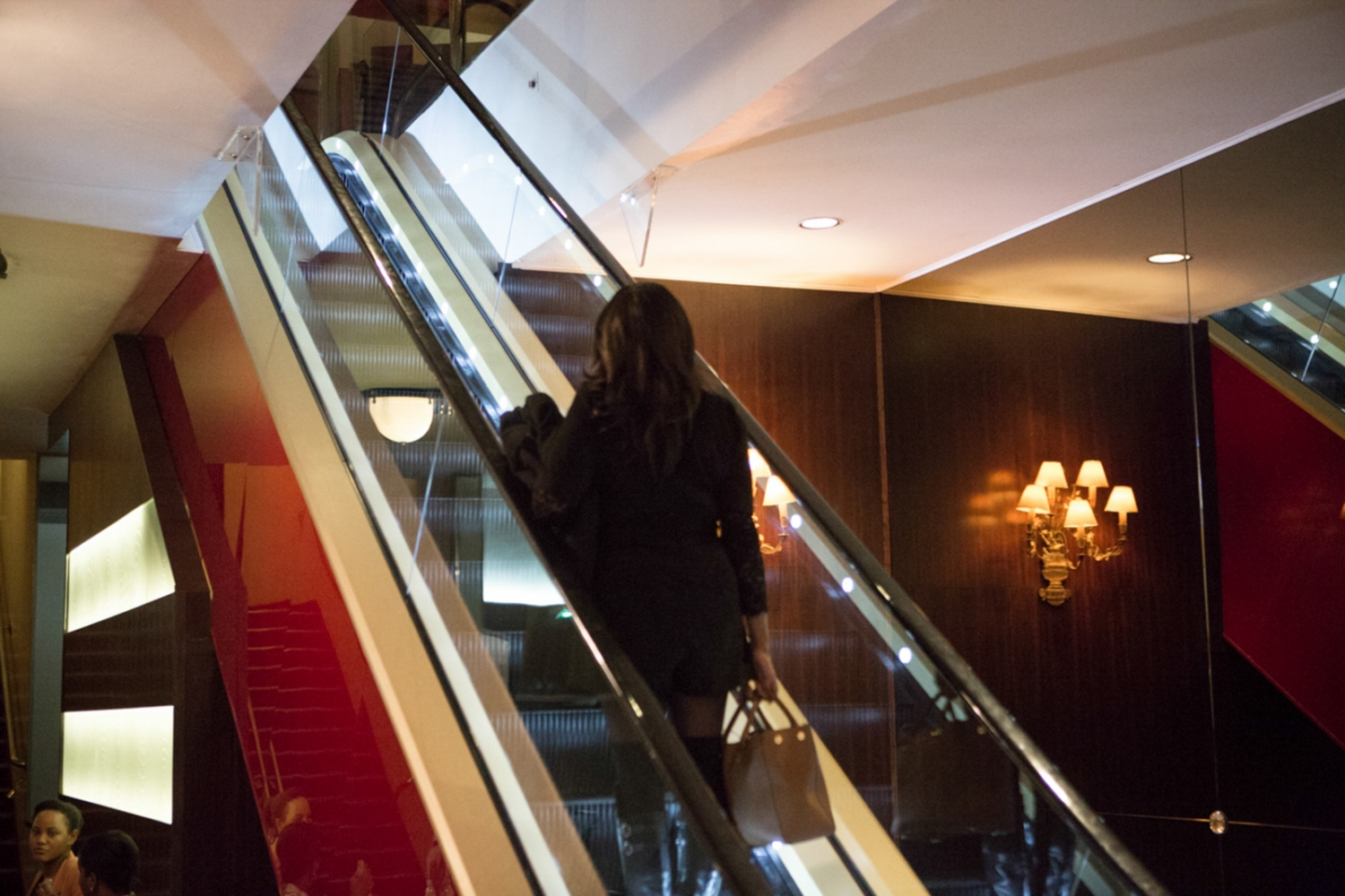 "A woman climbing up an escalator in Rex Cinema in Paris during the ""Brown Sugar File Festival"" , a festival of only Afro descendent movies playing, directing and producing. Paris, Ile de France, France"