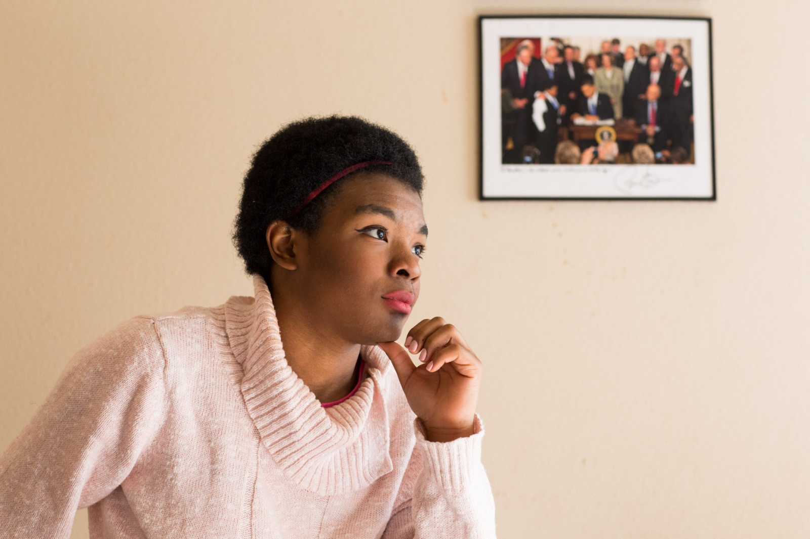 "Marcelas Owens, 17, at her home in Seattle, Washington. A photo of Marcelas and Barack Obama hangs on the wall behind her and is signed by Obama ""To Marcelas- You helped make history at an early age! Barack Obama"".  For CNN Digital"