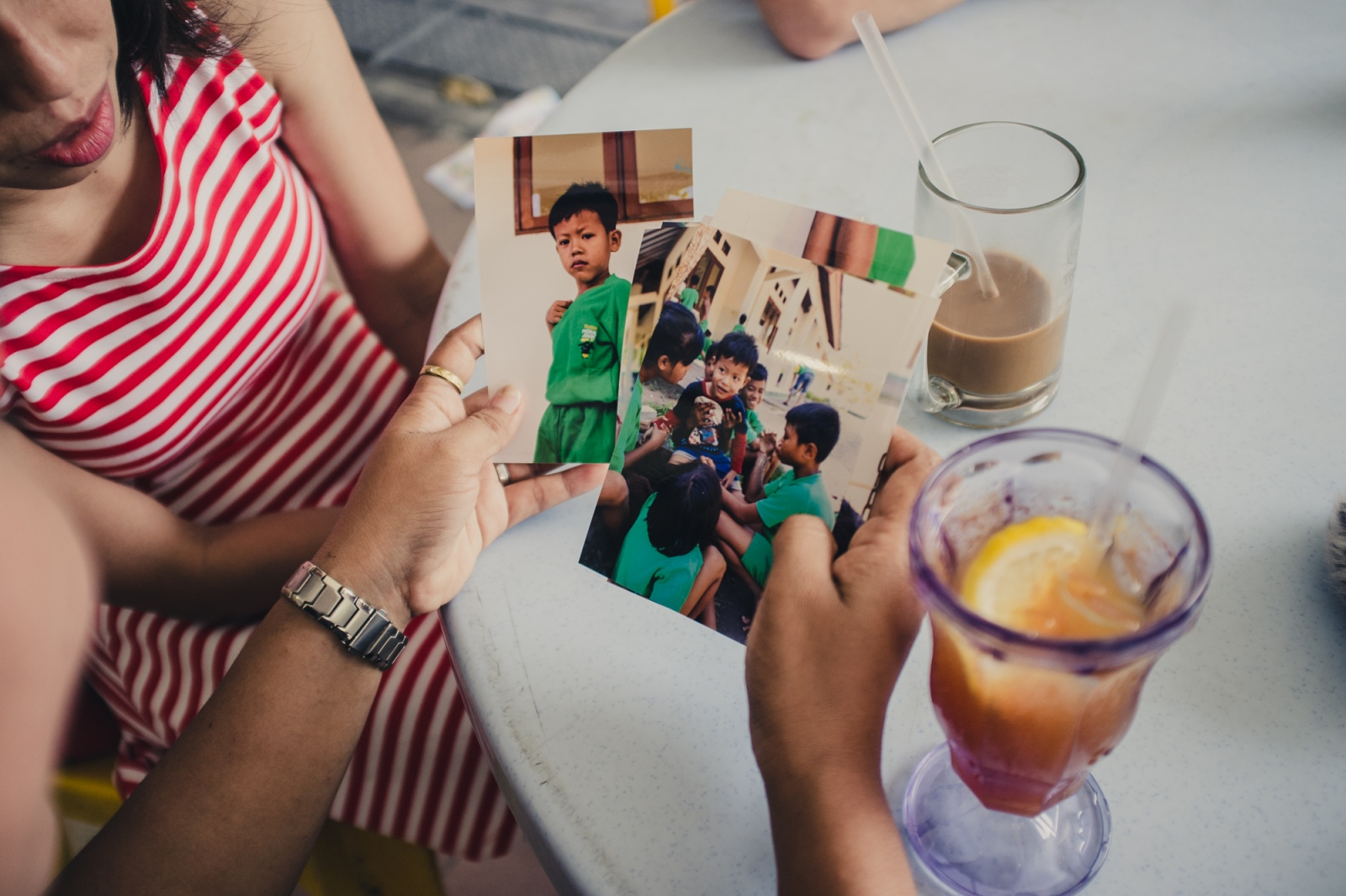 An Indonesian Foreign Domestic Worker with photographs of her 3 year old son in Indonesia. The father is absent and he is being looked after in a care home.  Scared of her family's reaction to her having a child out of wedlock she had left her son with another family when he was 18 months old so she could take up a job in Singapore. After the couple began to demand more money from her and refused to let her talk to her son she was granted time off from her employer to take her son to a care home run by the organisation Peduli Anak. The boy has minimal language skills and displays symptoms consistant with autism. Peduli Anak does not have the facilities to deal with autistic children and is hoping to help her find proper care for her son.