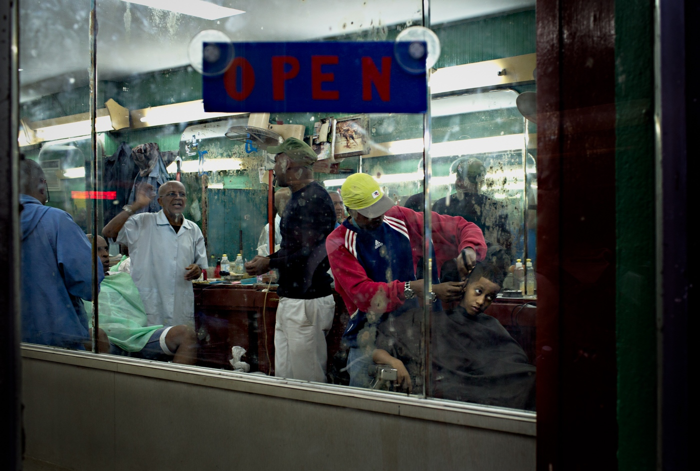 Barbershops are a social meeting place in Havana.