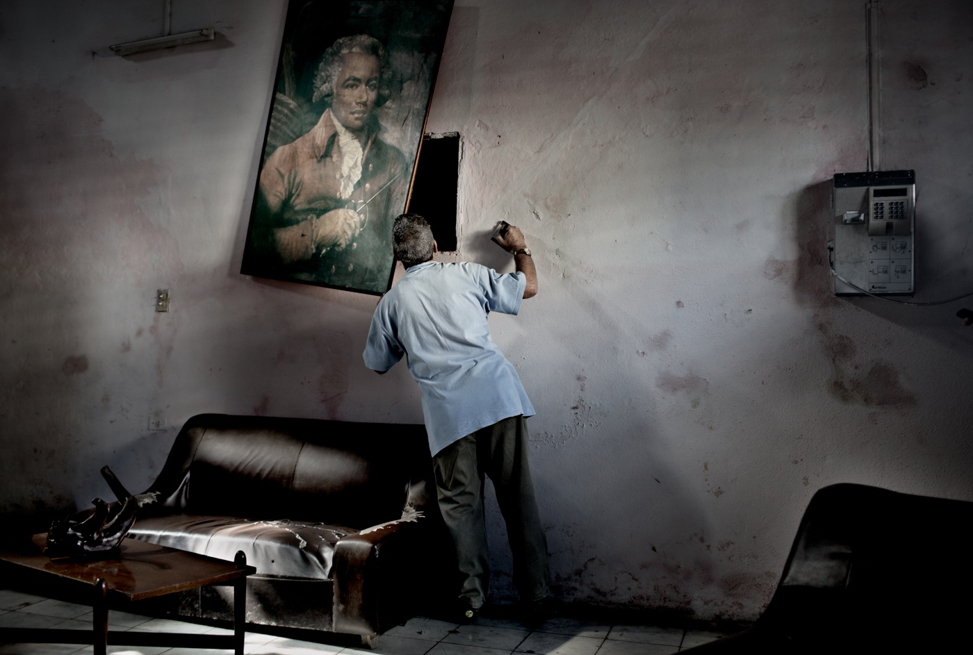 A man looks behind a painting at theLaura Alonso Dance Academy to read the water meter. Laura Alonso Academy is an offset of the National Ballet. To date, most of its graduates have defected to various countries outside of Cuba. The Academy functions mostly on donations as the funds for the arts are mostly spent on the National Ballet.