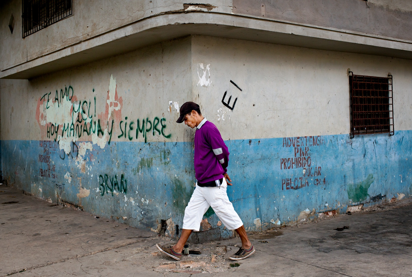 "A man walks past a wall with graffiti which reads: ""I love you Meli. Today, Tomorrow and Always - Bryan"" in a neighborhood in Havana."
