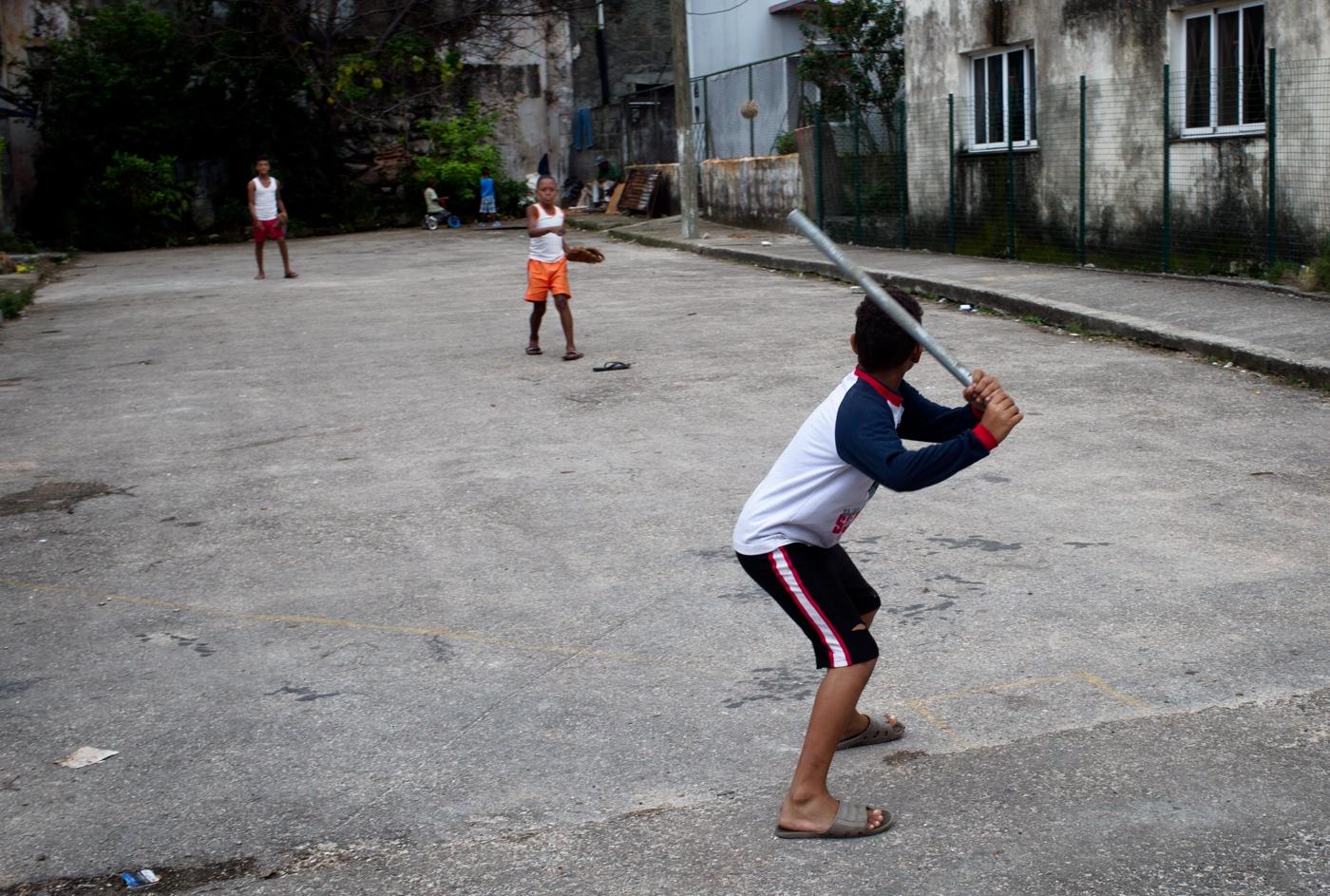 "Neighborhood kids play ""four corner"" baseball in a dead end street using a metal pipe as a baseball bat. Baseball is a national pastime in Cuba."