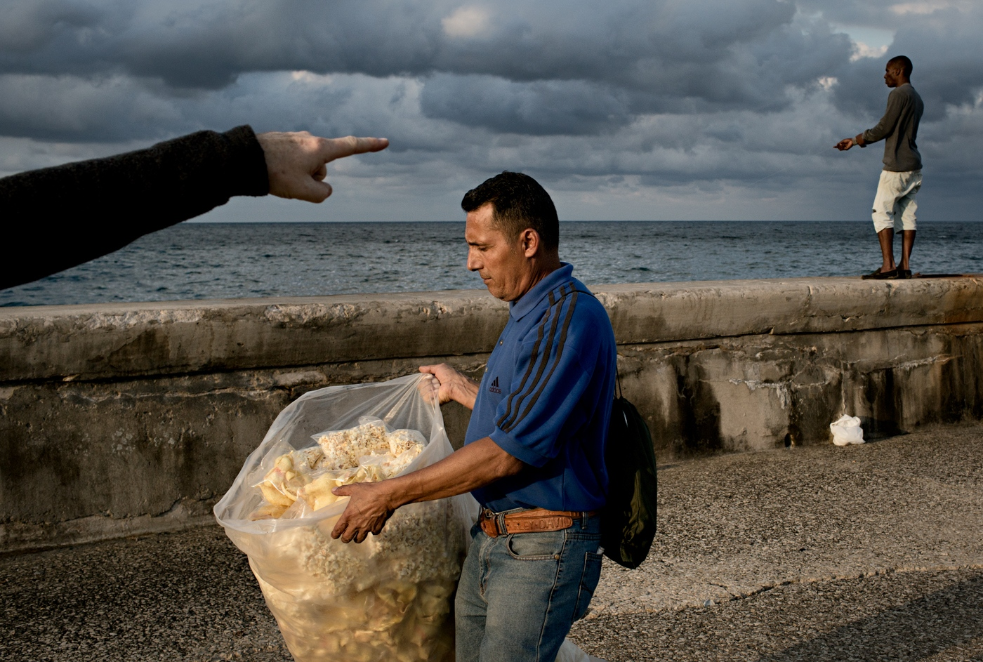 A man sells homemade popcorn to tourists, lovers and fishermen on The Malecón. The Malecón (sea wall) was first built in 1901 and then was expanded. The main purpose of it was to protect the City from the ocean waters-aside from that, it now is a major promenade space for families, lovers, prostitutes and fishermen.