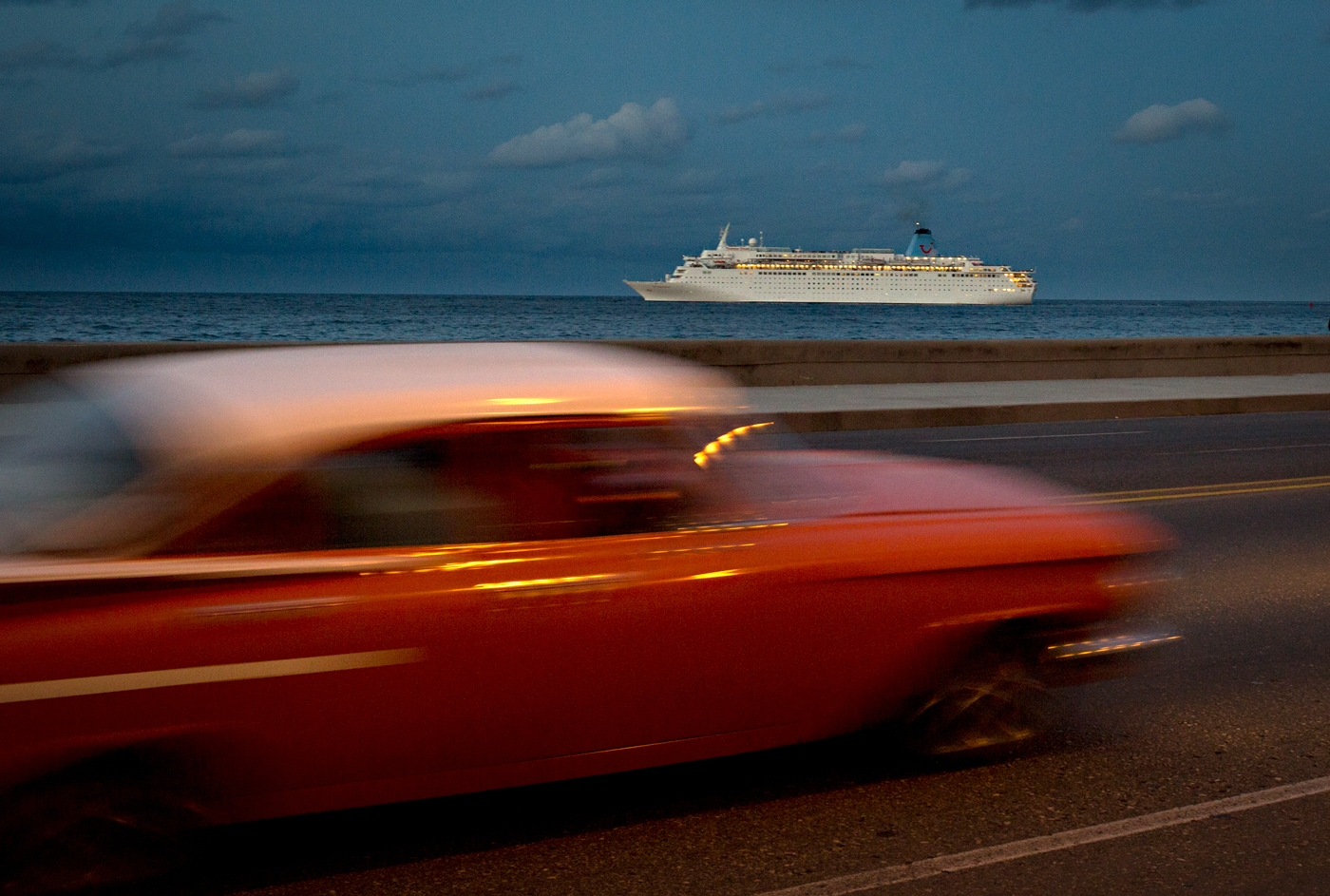 A luxury cruise ship navigates its way slowly in Havana waters passing in front of The Malecón. The Malecón (sea wall) was first built in 1901 and later was expanded. The main purpose of it was to protect the City from the ocean waters-but aside from that, it now is a major promenade space for families, lovers, prostitutes and fishermen.