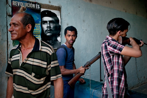 Young men shoot pellet guns at a makeshift stand in a Havana street.