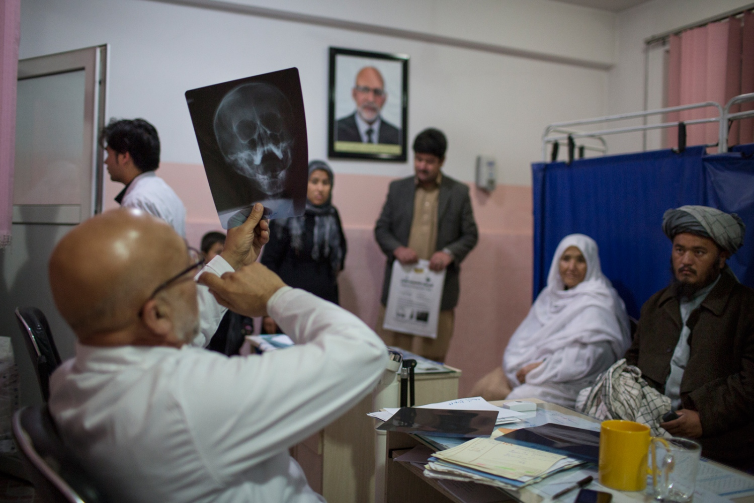 With a continuous stream of outpatients to attend to there is little or no privacy. Patients and their relatives are called into the consultation room where diagnosis and treatment are discussed in the presence of others waiting their turn. Doctors use basic tests and X-ray to eliminate other potential causes of health problems. Male patients have their vital signs checked behind the screen. Mazar e Sharif, Afghanistan. December 2015. Photo: Magda Rakita/BAAG