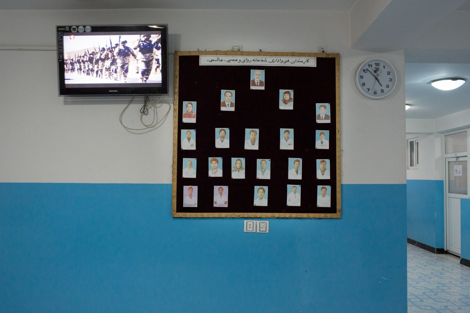 The main hall of the hospital with a notice board that displays portraits of staff members. Doctor Alemi has on-going problems with recruiting qualified staff. Some of his junior doctors want to leave Afghanistan. He has managed to convince some of his children to take an interest in the hospital, where they now work. Mazar e Sharif, Afghanistan. December 2015.