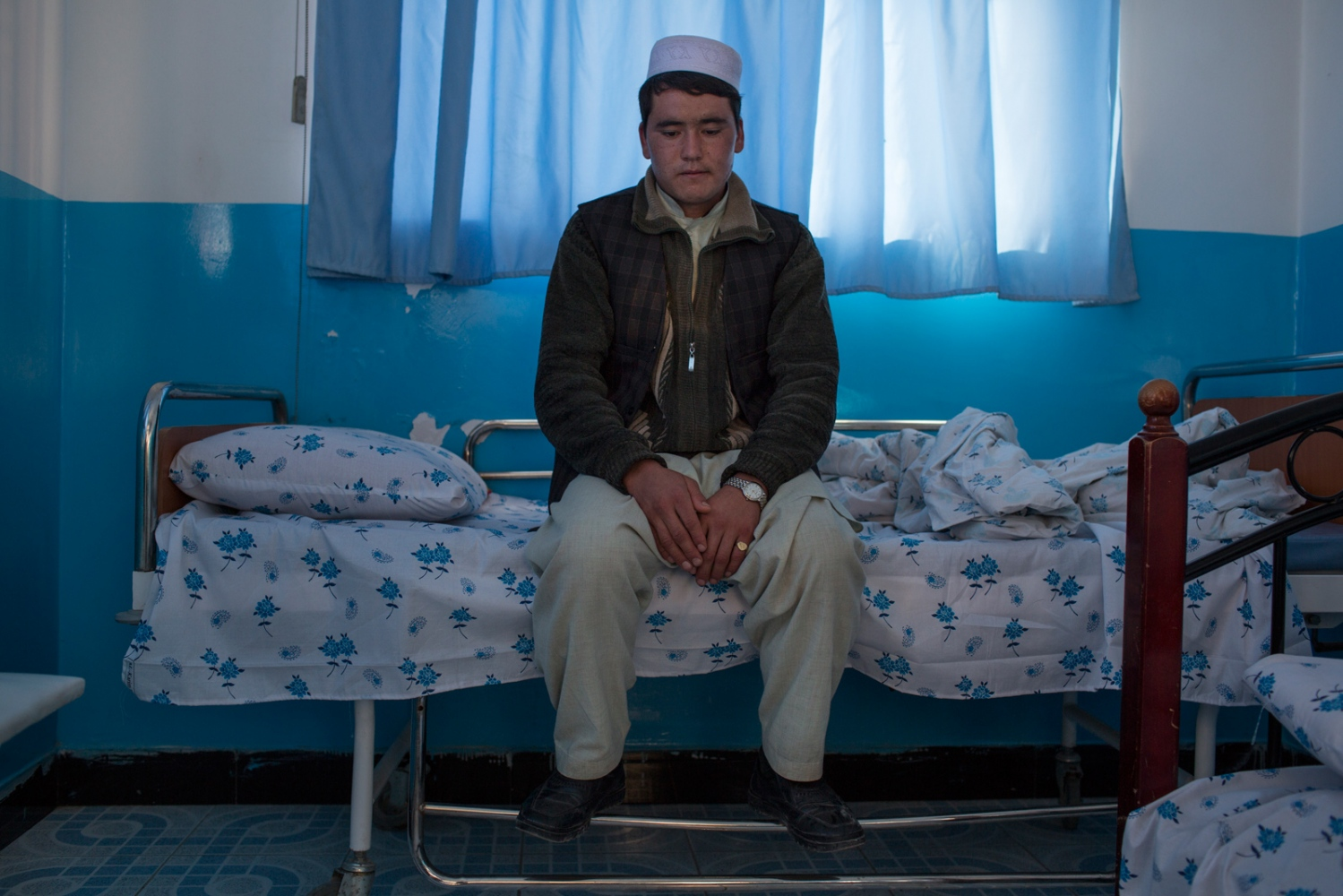 Mohammad sits on the bed while his mother - Bibi Oghel – rests. Mohammad says she was very worried and unable to communicate. Relatives can stay overnight in the same room as those they accompany. One night stays in the hospital cost 1500 Afghanis (about $23) and some families borrow money to cover these costs. Mazar e Sharif, Afghanistan. December 2015.