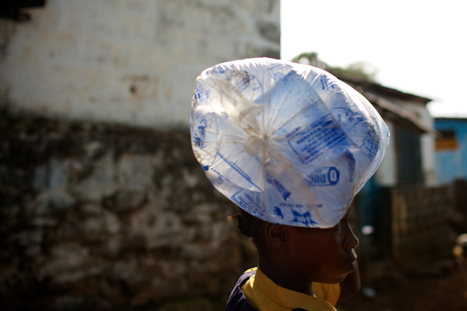 Monrovia, Liberia. April 2013. A girl carries bags with fresh water to be distributed at school during lunch time. The school, like many others, has no running water or toilets.