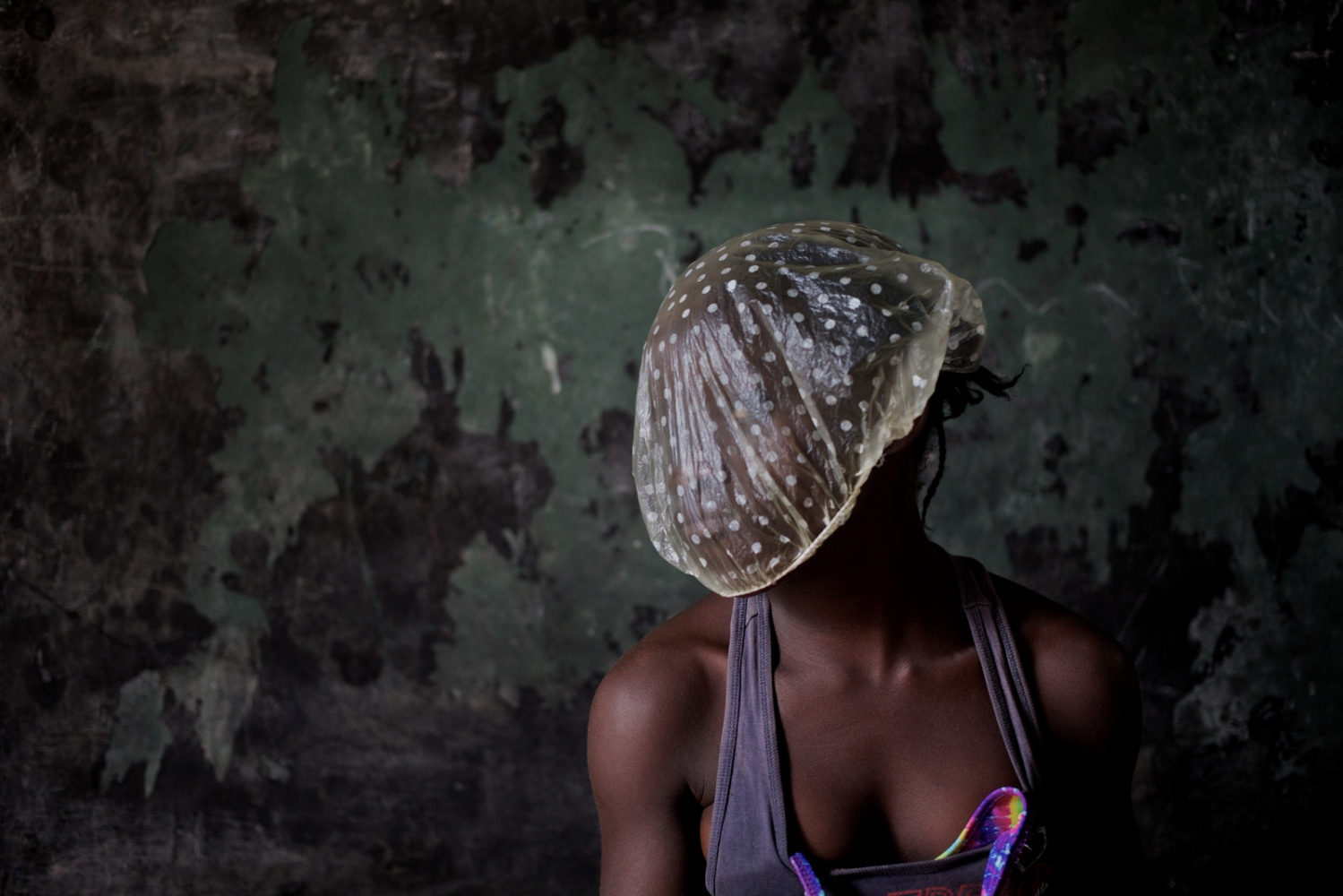 Monrovia, Liberia. July 2013. Girl plays with a shower cup used during the rainy season to protect hair.