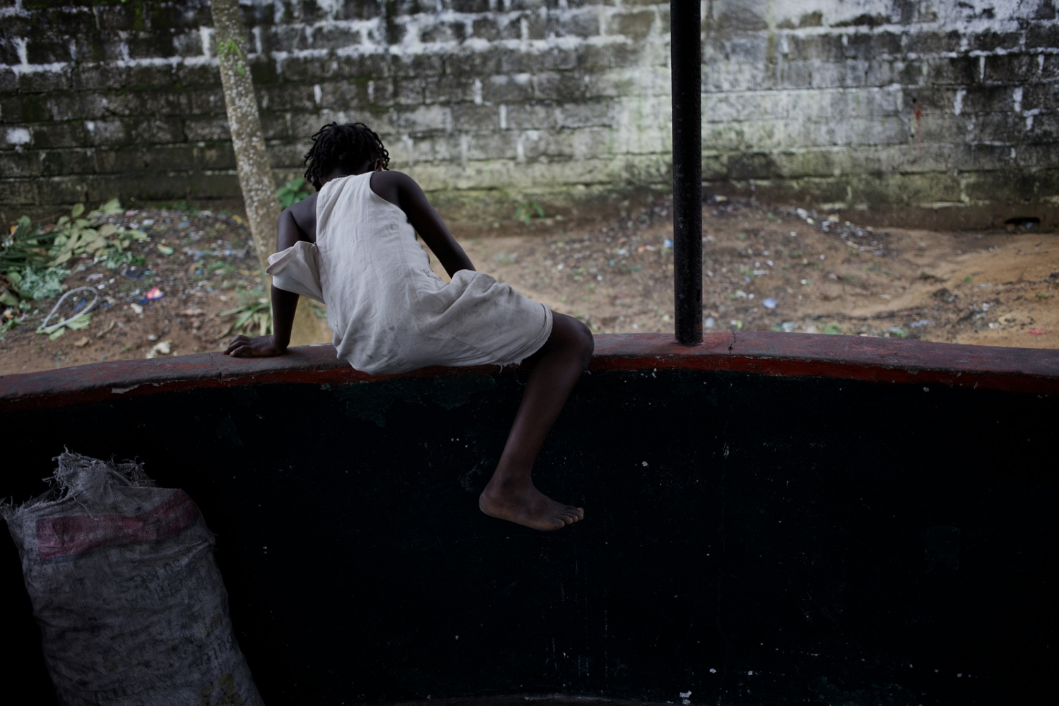Monrovia, Liberia. July 2013. A young girl jumps over the fence dividing kitchen area from rest of the compound of the safe house for survivors of sexual and gender-based violence.