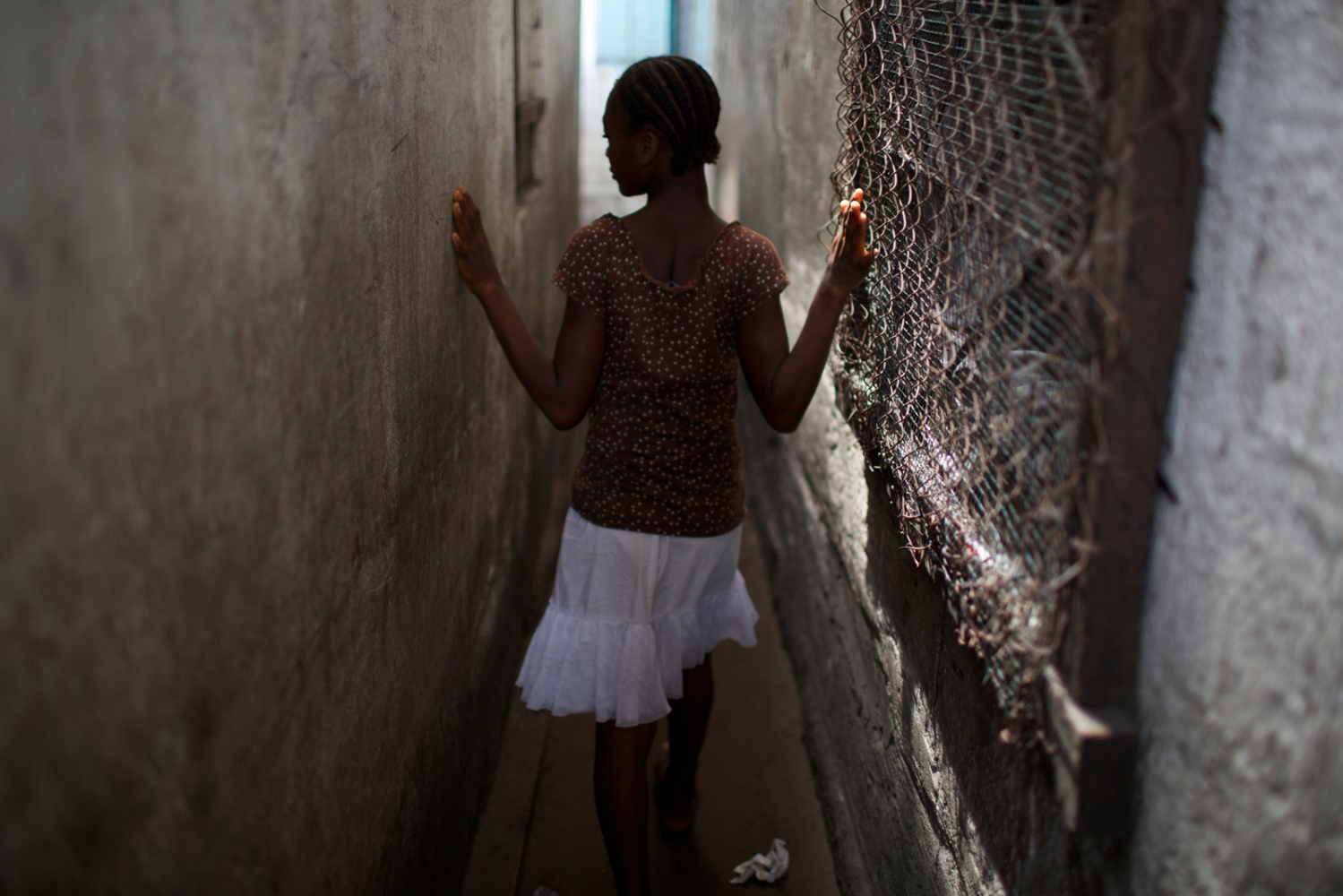 Liberia, Monrovia, West Point. April 2013.  Evon walking in the alleyways of West Point.