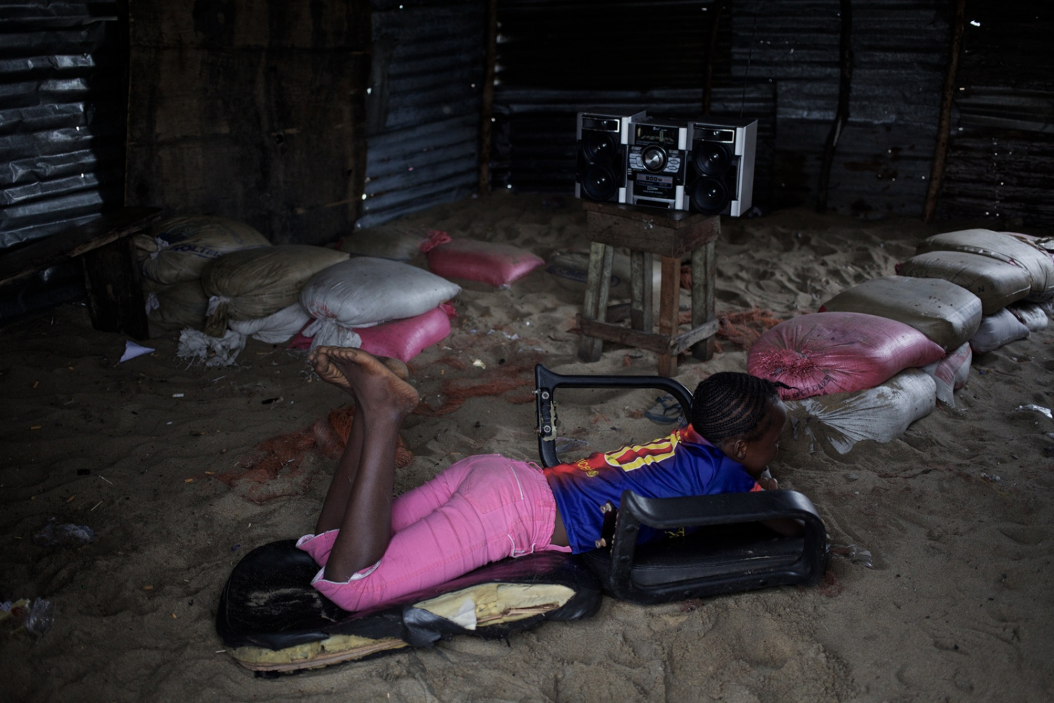West Point, Monrovia, Liberia. August 2013.  Girl relaxes in the bar where she works.