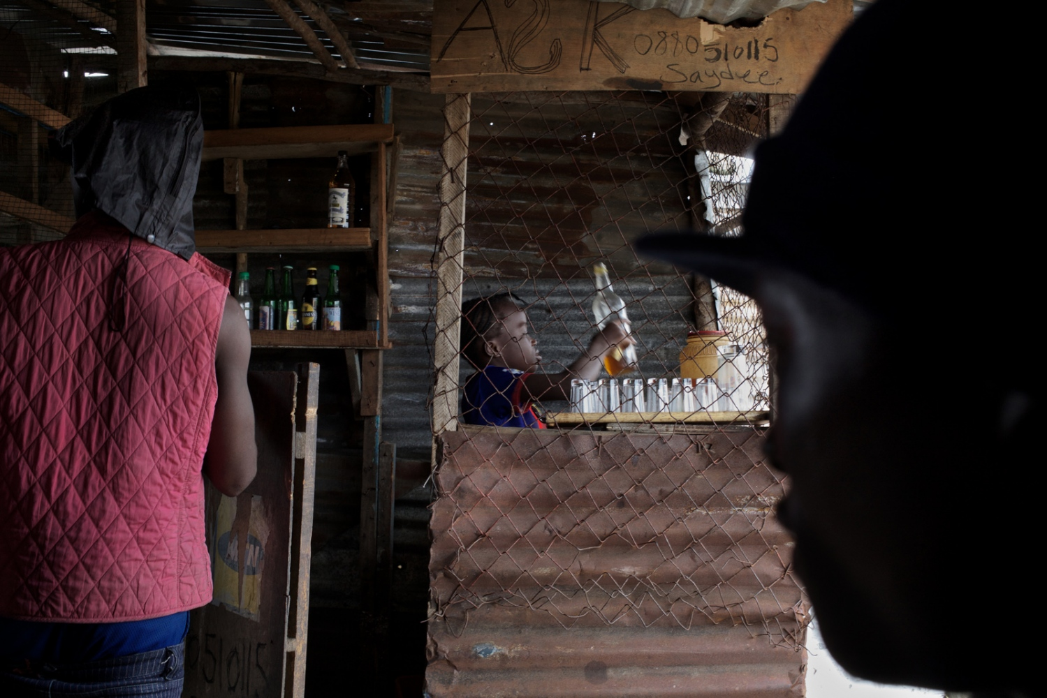 West Point, Monrovia, Liberia. August 2013. A young girl works in a bar run by her guardians.