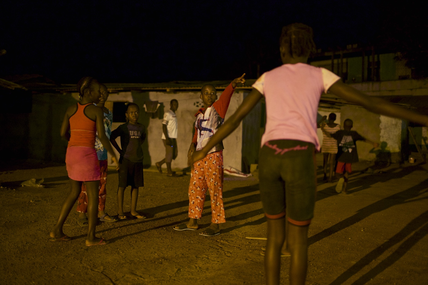 Monrovia, Liberia. 09 August 2015. Children play late at night outside a restaurant popular with wealthy Liberians and expats. As the restaurant is using a generator to light up the parking spaces the surrounding area became a popular place among local population to hang out at night as they can't afford access to electricity.