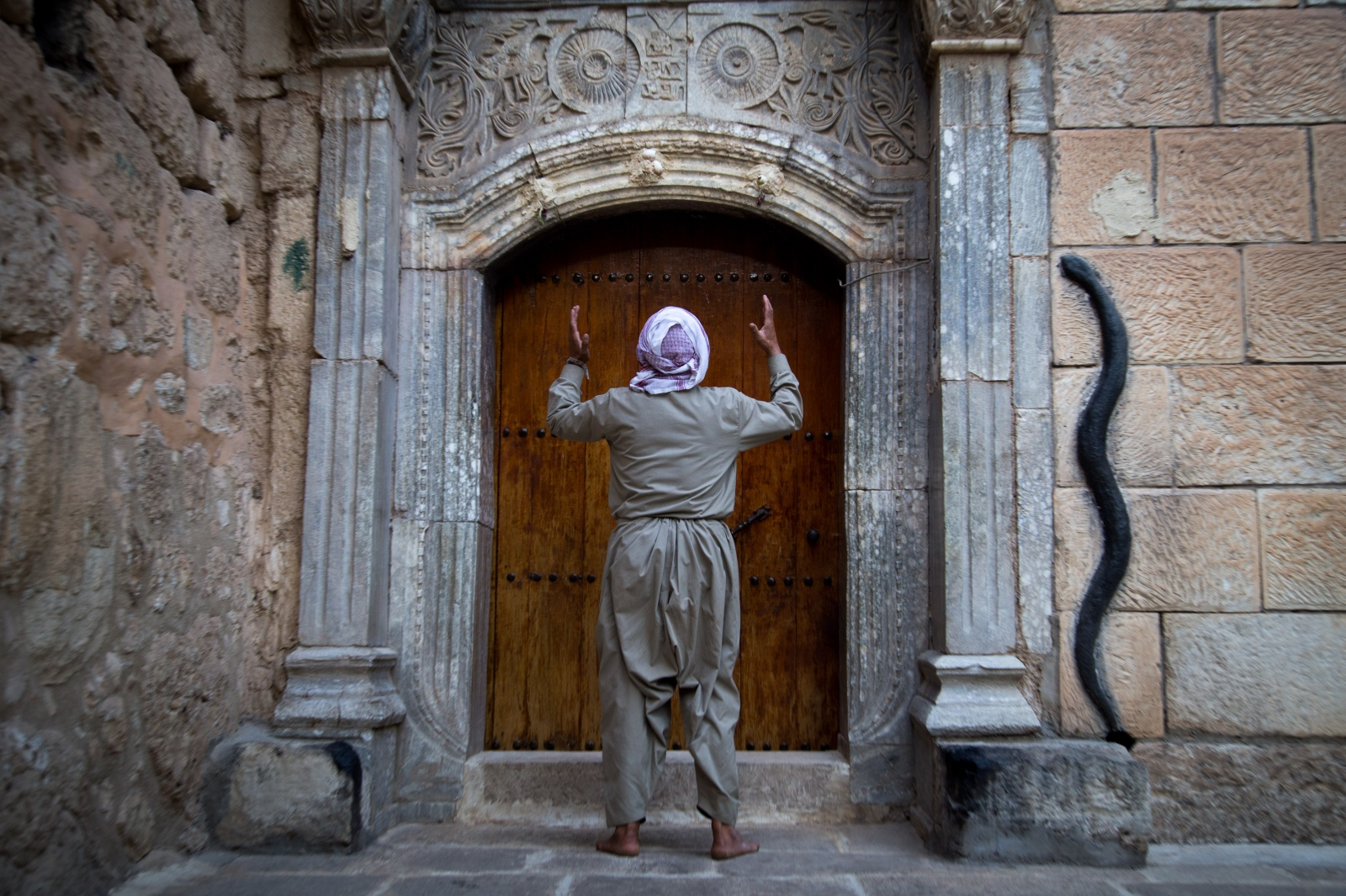 A Yazidi man prays at the entrance to the holy shrine in Lalish, Iraq.