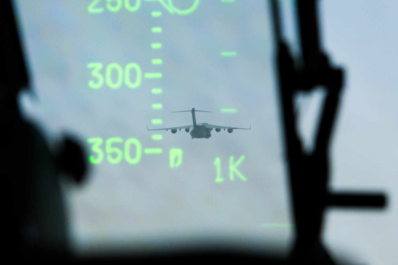 The heads-up display in a C17 cockpit shows a leading C17 over the Atlantic Ocean enroute to Senegal.