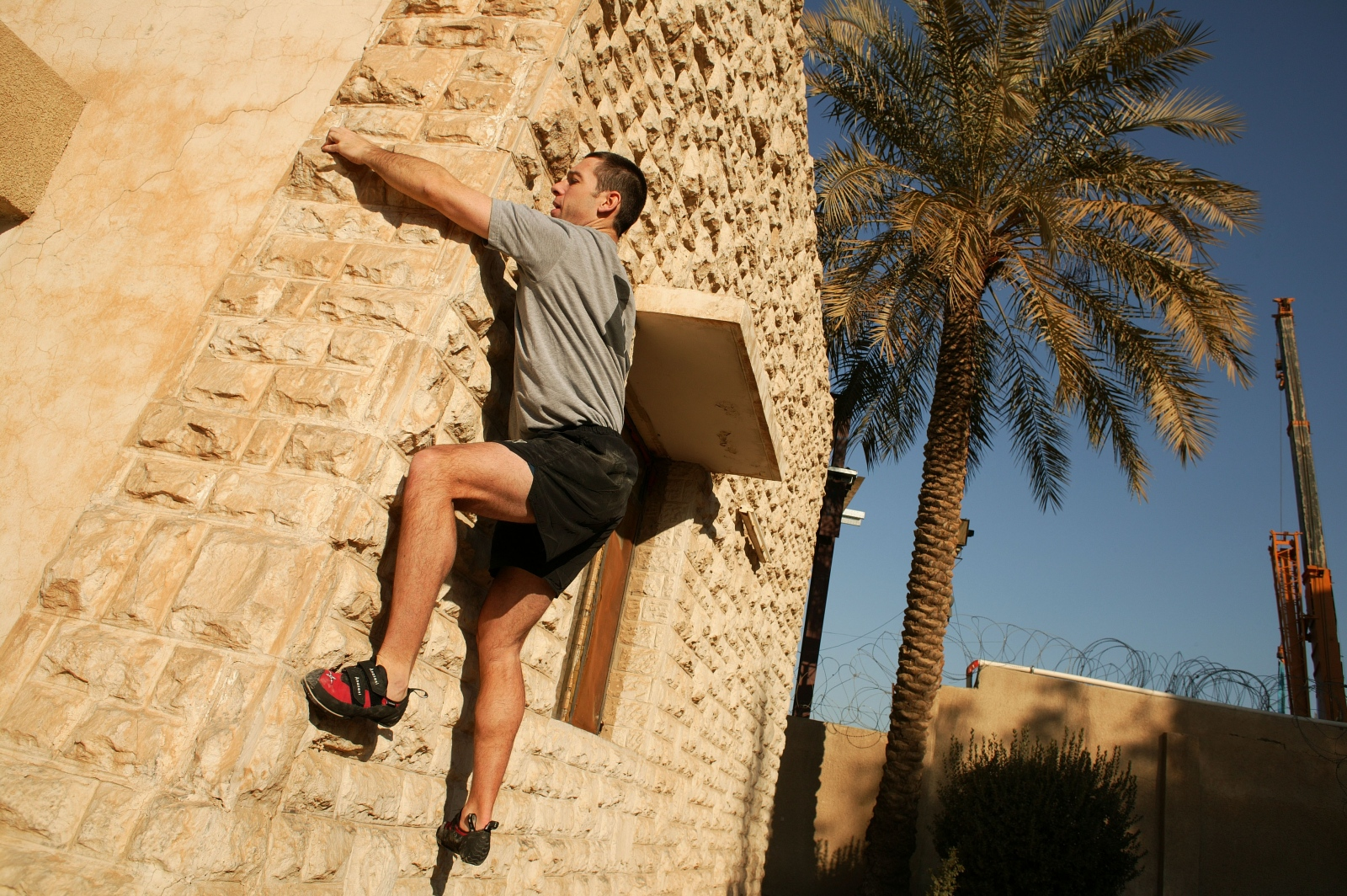 CPT David Hile, MD, an emergency physician with the Baghdad Combat Area Support Hospital climbs the wall of a residence building to stay in shape and reduce stress.
