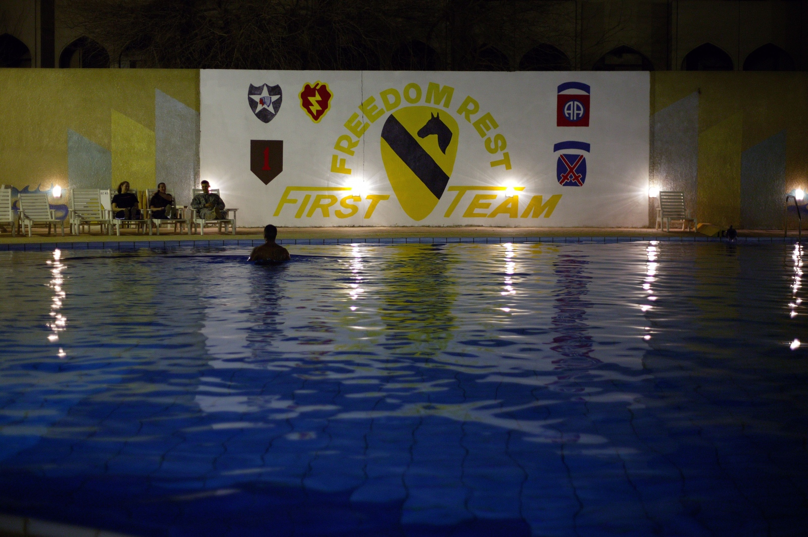 A U.S. soldier swims in a pool on the grounds of the former Iraqi Republican Guard Officers Club