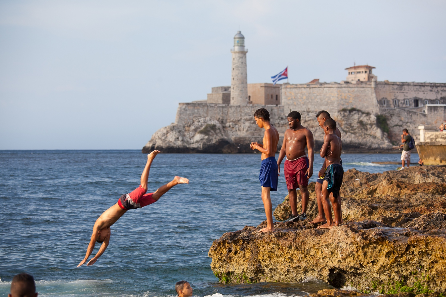 Despite having so little, kids revel in the limited freedom they have. Here, boys jump from the wall along the Malecon, with the old fort Castillo del Moro in the background.