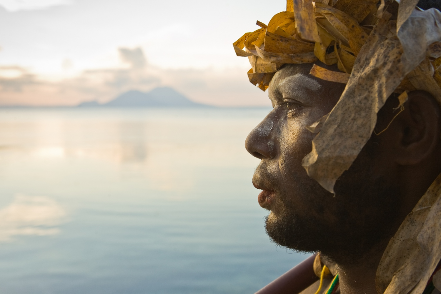 A local man reprises traditional costume, with sacred Tavurvur volcano in the background.