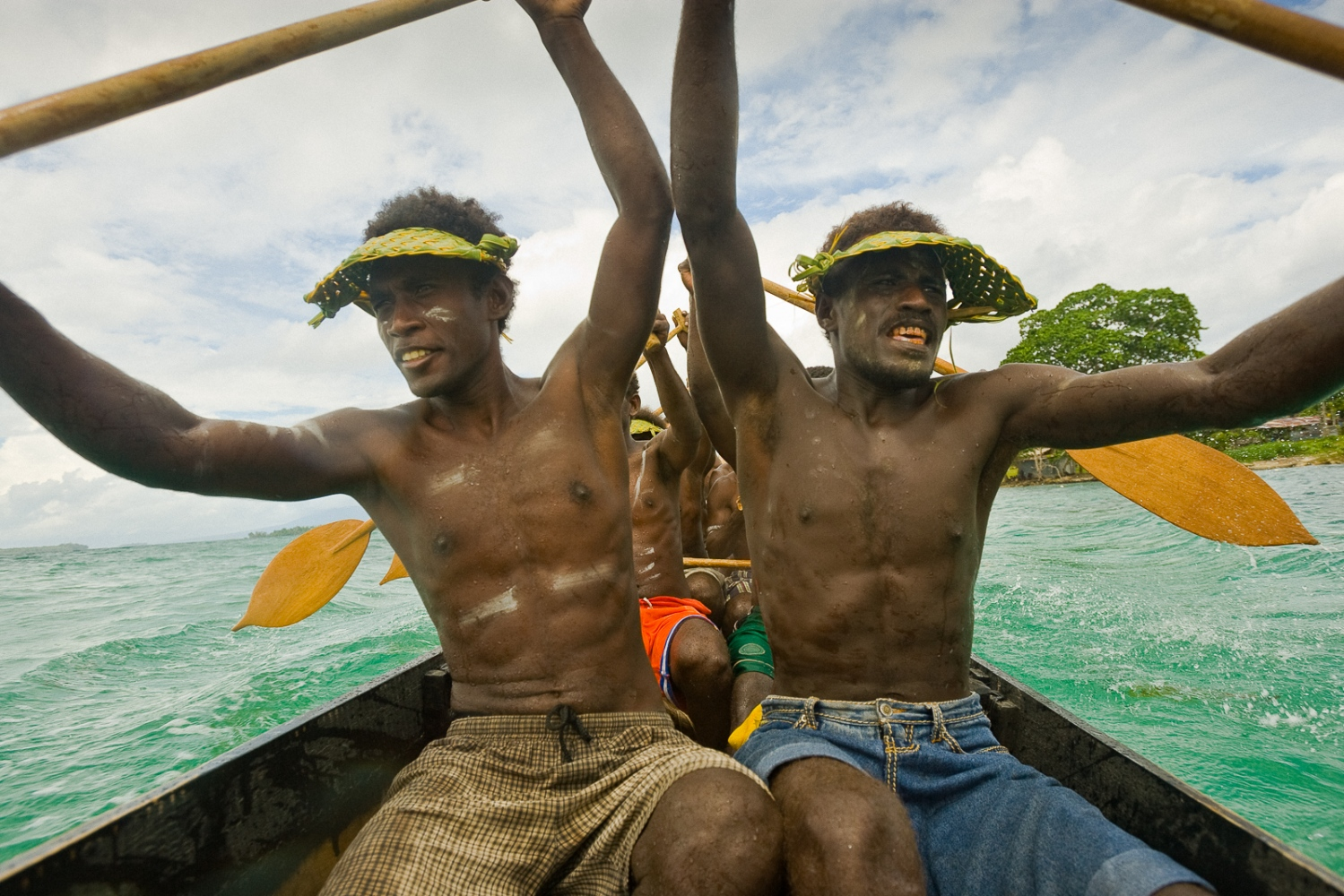 All hands on deck during the launch of a traditional war canoe, these days used for Christian religious celebrations. Munda, New Georgia Island in the Solomon Islands.