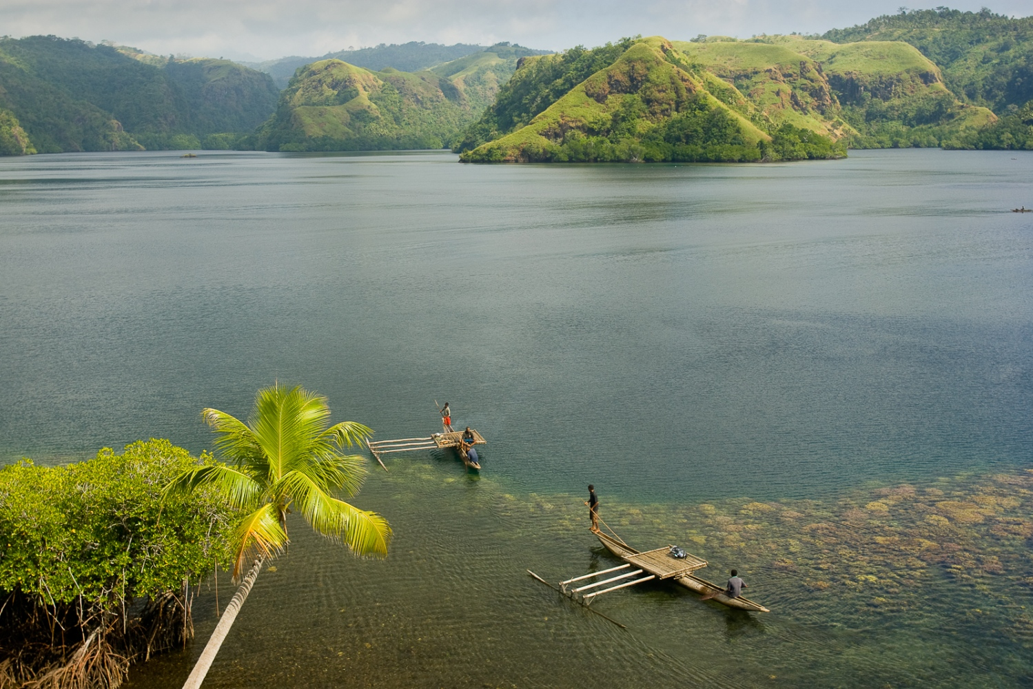 "This is what a healthy coral reef looks like. Locals near Tufi in the Central Province guide their outrigger canoes through ""rias"" or fjord-like waterways in this pristine environment."
