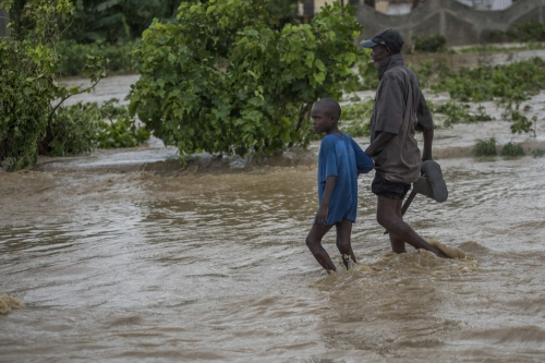 A man with his son are crossing the flood river of Léogâne