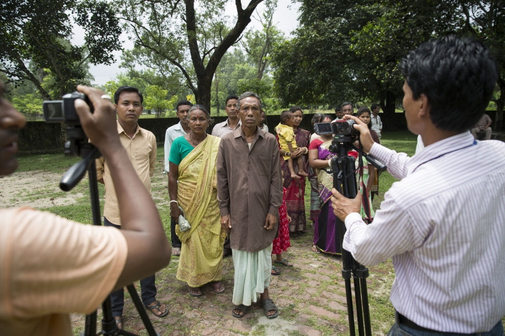 An extended family arrive at a government compound in the town of Debiganj to sign documents and filmed by local TV journalists. Originally they asked if they could go to India after the disbanding of the enclaves but later changed their mind and decided to stay. Their request was allowed and formalised on this day.