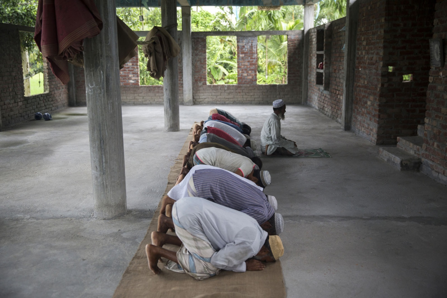 Muslim men from the Dhoholakhagrabari enclave pray in their mosque. The only solid structures that exist inside the enclaves, that aren't made of jute sticks and bamboo, are mosques. People have not risked building solid structures for housing due to the uncertainty of their situation and lack of roads to bring in the heavy material. With no outside help the locals collected donations and built this unfinished structure to use as their place of pray.
