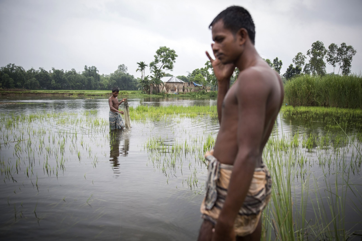 Bangladeshi men who lives very close to an enclave fish in a river swollen by rain. This part of Northern Bangladesh is very poor with most relying on fishing and agriculture to survive. Yet these man and their family will have electricity and be able to receive such things as basic health care and fertilizer subsidies. Those living in the enclaves will receive none of this.