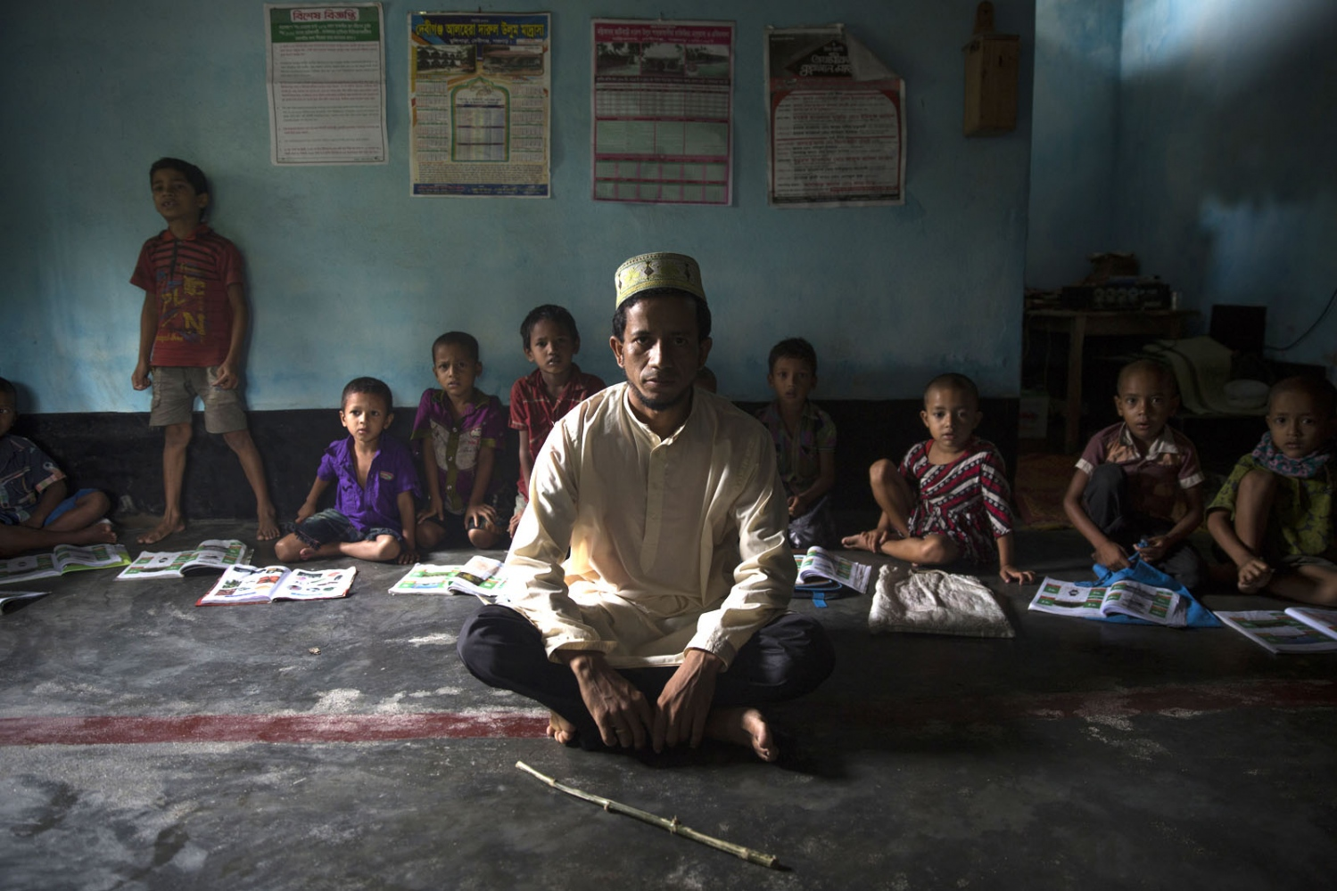 In Maja Para village in the Dhoholakhagrabari enclave young students and their teacher sit in class of a madrassa. Because enclave children have a difficult time accessing the education system in Bangladesh the locals of this enclave formed an Islamic Foundation funded on donations and built this school to give their children some form of education.