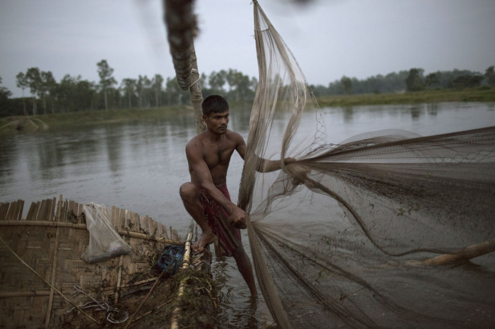 A Bangladeshi man fishes at dusk using his large bamboo fish trap. This river exists just outside the enclaves and as its in Bangladesh territory, enclave dwellers are forbidden to fish here otherwise angering the local fishermen.