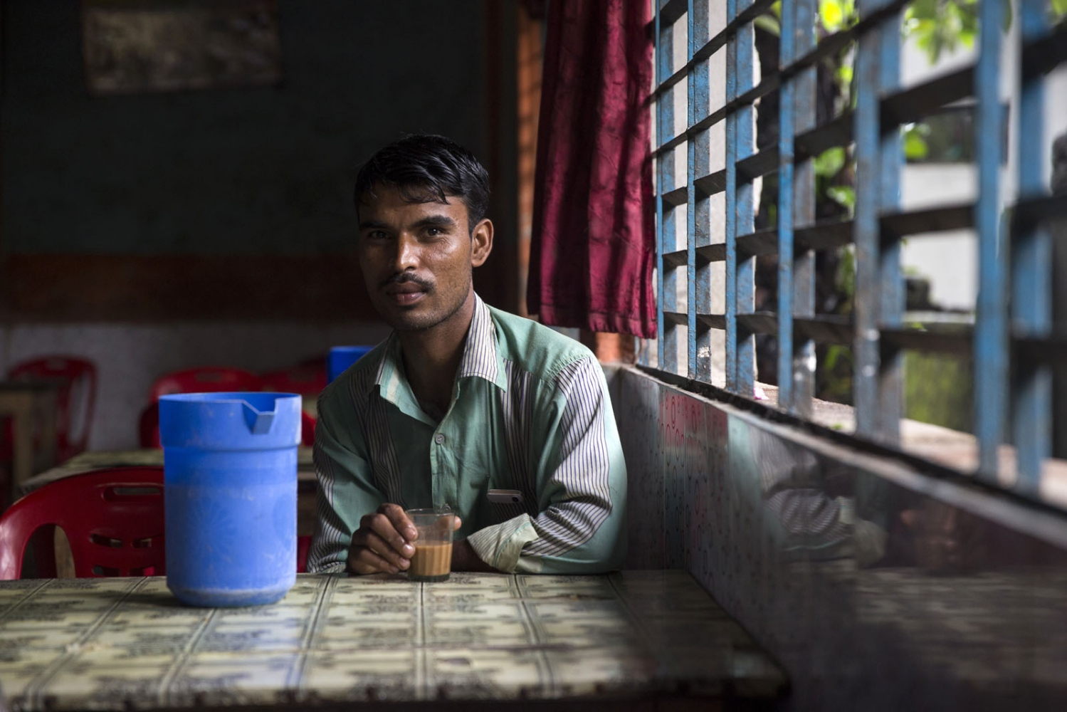 A Bangladeshi man has tea in a restaurant in town of Debiganj. Out of the 979 enclave dwellers that decided to leave for India the district of Debiganj has 406 of them being surrounded by large enclaves.