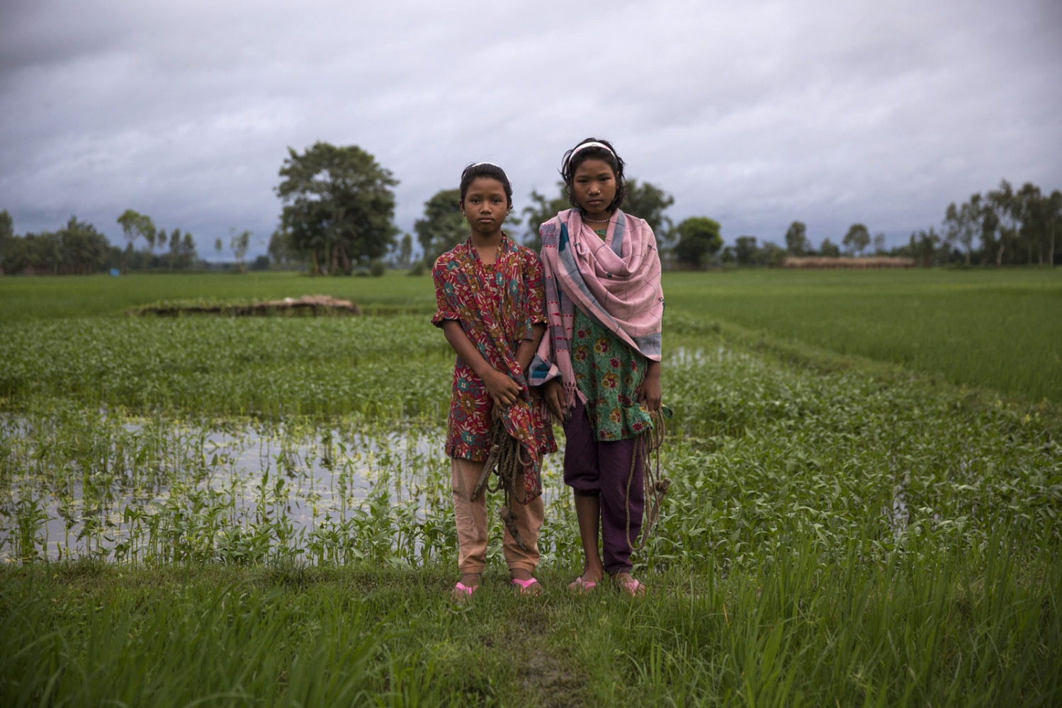 Sisters Lobar Rani Bormoni, 11, (left) and Shapla Rani Bormoni, 12, stand in a paddy field just outside their village of Ponchoki Bhajini located inside the enclave of Dhoholakhagrabari. Out of the 22 families in their village on 2 families will remain in Bangladesh, the rest including the girls, will move to India to start a new life.
