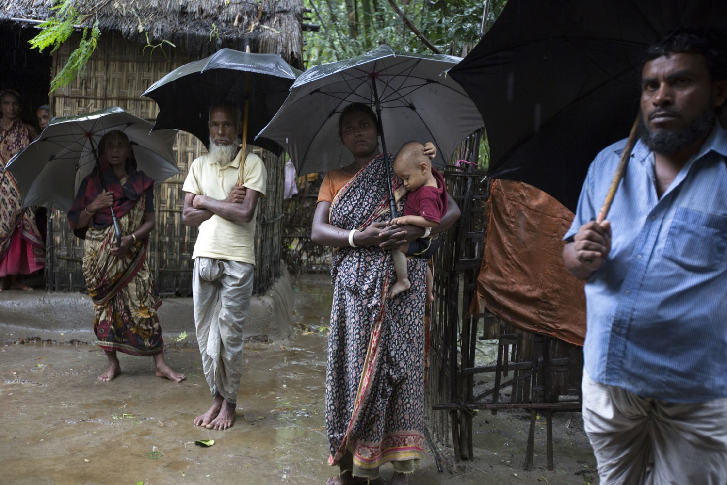 Residents of an enclave called Dayuti shelter from rain under umbrellas. This relatively large enclave with a small population has fallen victim to powerful Bangladeshi families who have moved in to the enclave to grow eucalyptus evicting any local residents in their way. Because the Bangladeshi police have no jurisdiction in the enclaves the locals are powerless.