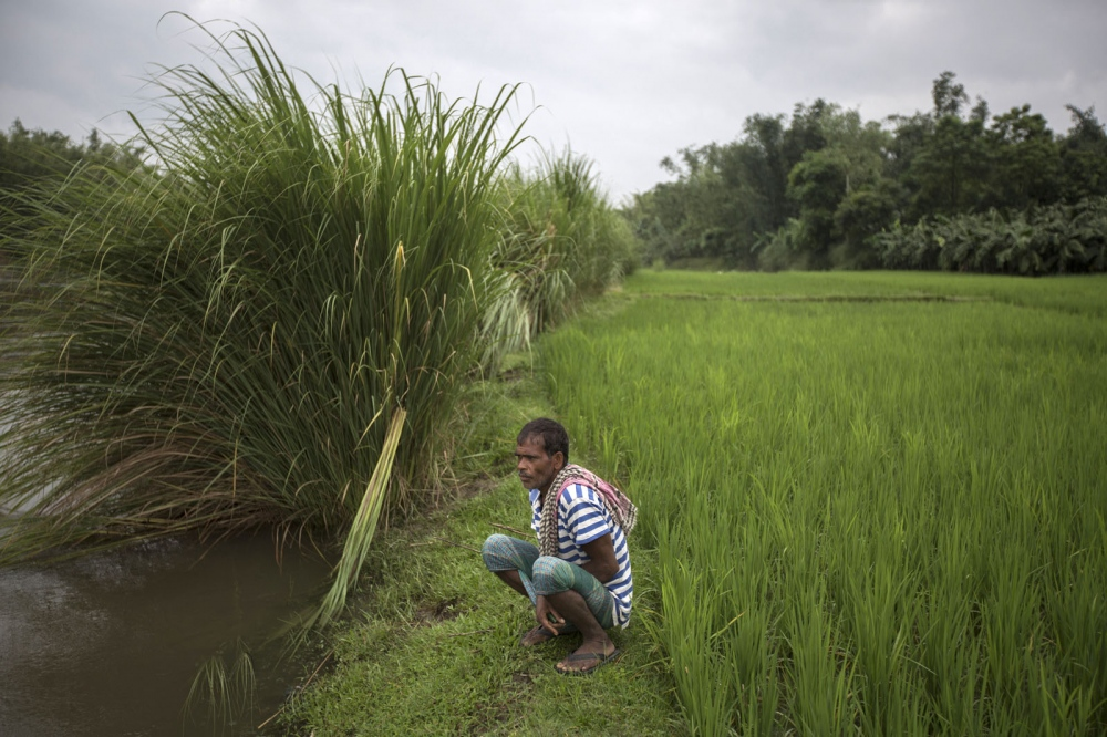 A Bangladeshi man who lives very close to an enclave squats next to a river in the early morning.