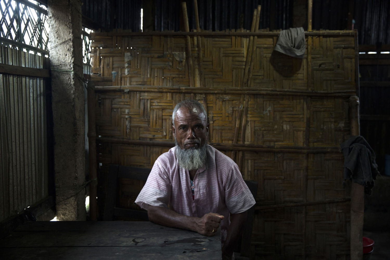 A Bangladeshi man sits in a shop in the market of a small town that sits between enclaves. There is very little distinction between land inside and outside an enclave but all the locals know know exactly where the boundaries lie.
