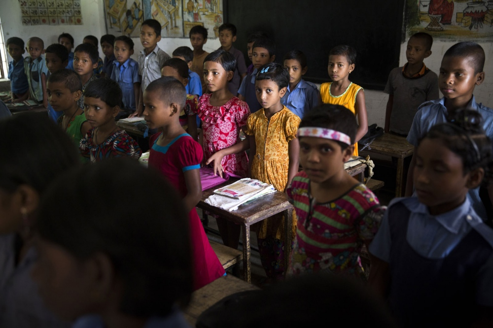 Rupsana Begum, 7, (pink and white dress) and Monalisa Akter, 7, (orange dress) are from an enclave but were able to come and study at Sher-e-Bangla Government school as a result of their parents managing to acquire fake documents and pay money.