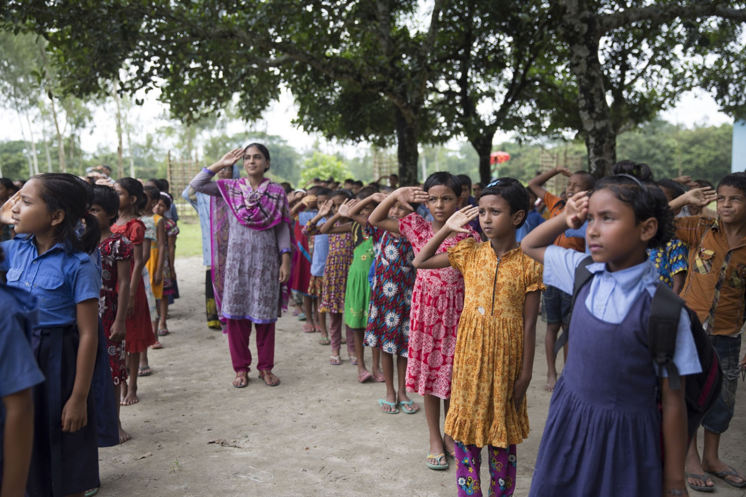 Rupsana Begum, 7, (pink and white dress) and Monalisa Akter, 7, (orange dress) take part in the daily raising of the Bangladeshi flag at Sher-e-Bangla Government school. They are both from an enclave but were able to come and study as a result of their parents managing to acquire fake documents and pay money.