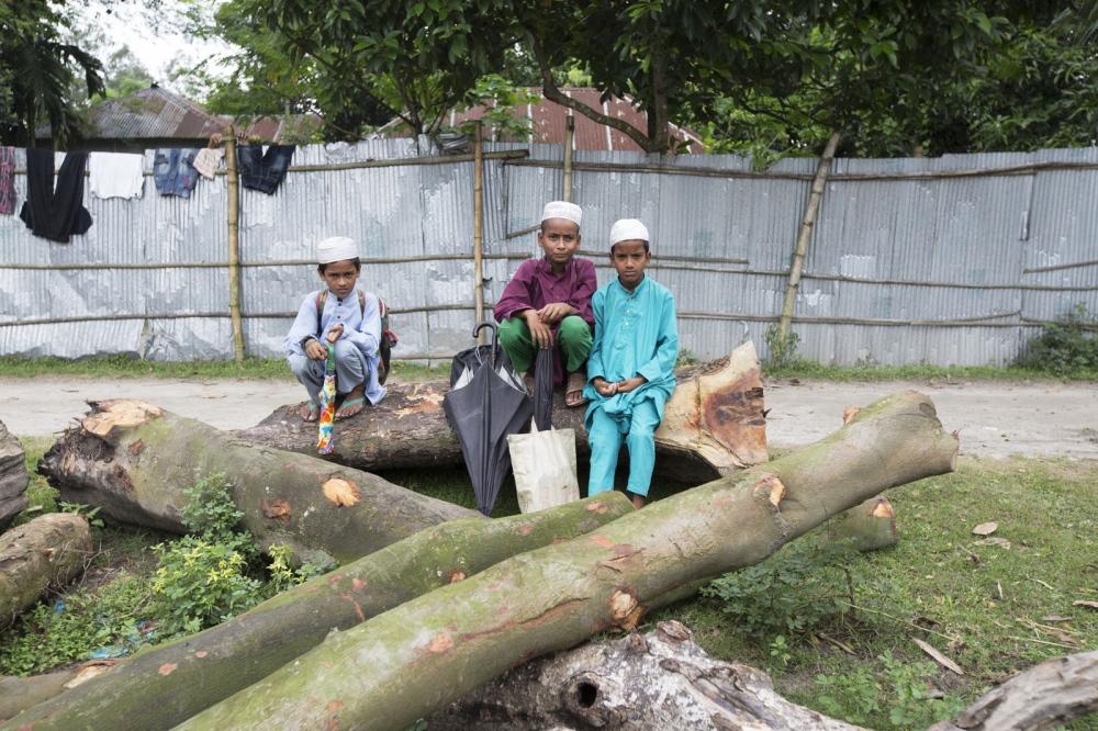 Local Muslim boys take a break between school on the logs of a saw mill in Debiganj town.