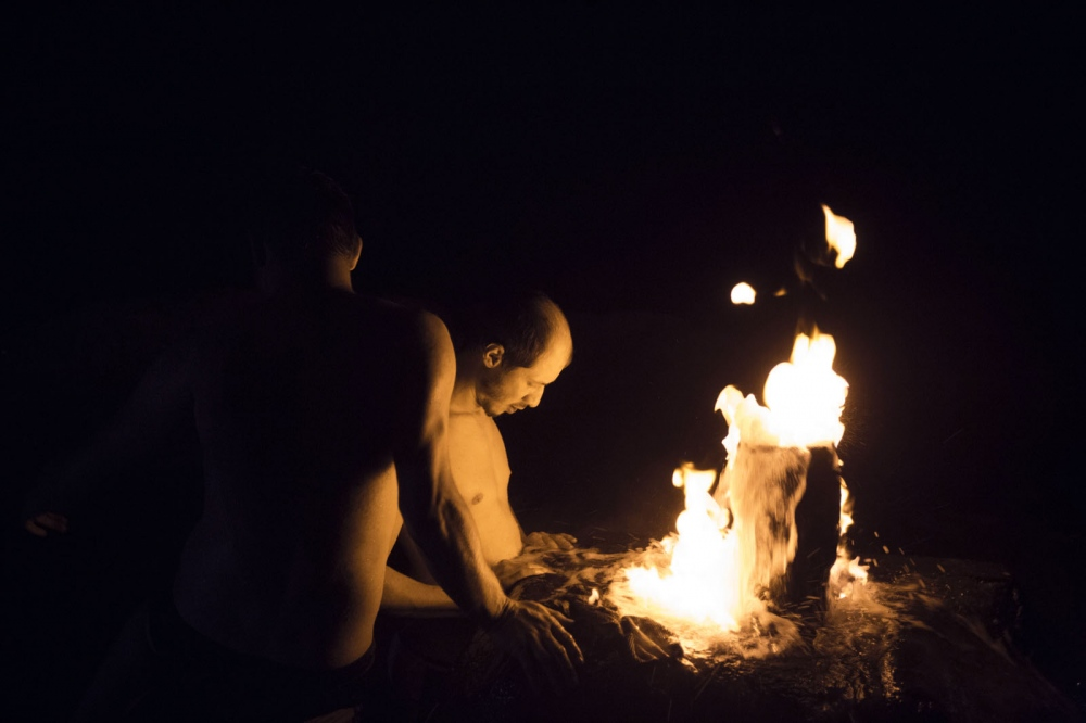 After a party, young Dagestani men visit a hot springs in the middle of no-where which has a flammable fountain of water.