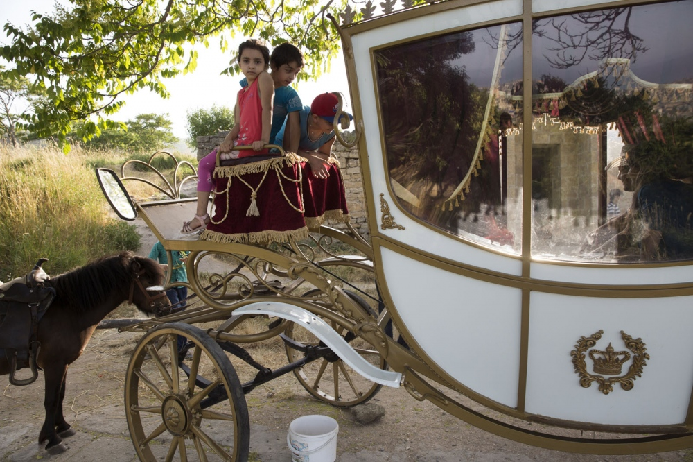 A young girl and her family play and take photographs on an imitation of a princesses carriage inside the ancient citadel at Derbent.