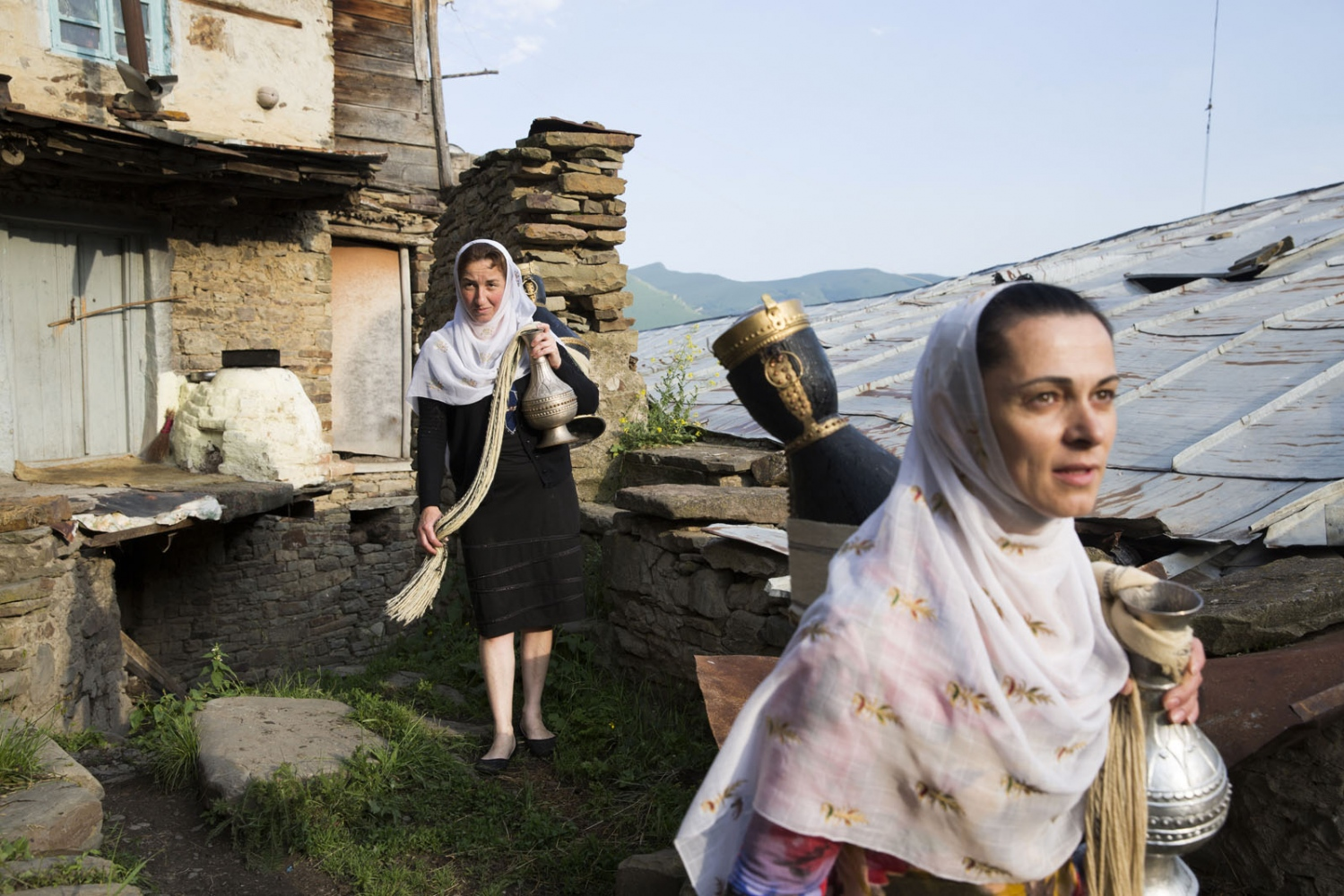 Two local women walk through the old town of Kubachi after having collected water from a local spring. A very traditional village, the women still use the old original containers to collect the water. The village inhabited by people of the Dargin ethnic group is famous throughout the whole of Russia for its skilled silver craftsmen who are commissioned from across Russia and abroad.