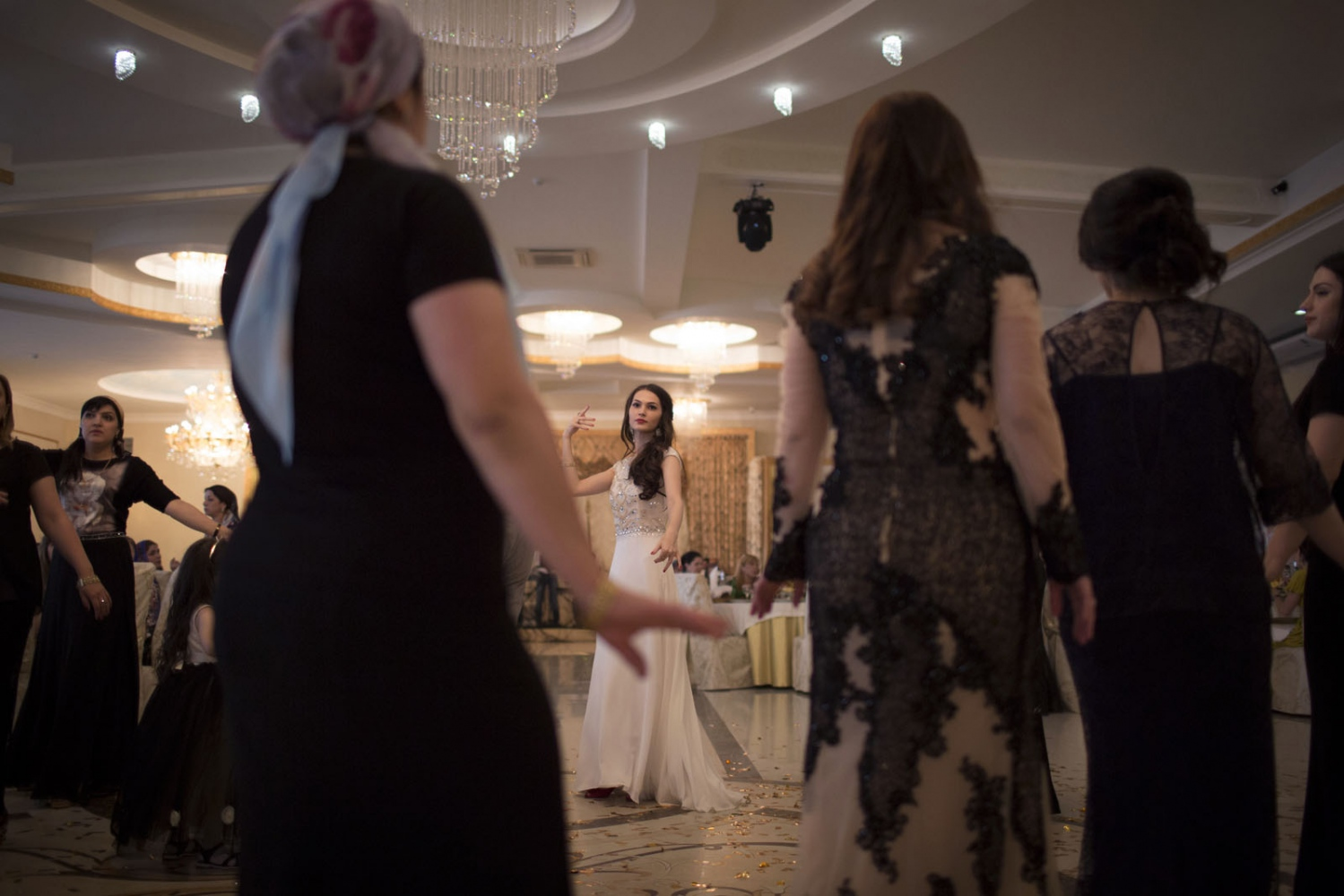 Dagestan men and women dance on the dance floor during a wedding in an expensive wedding hall in Makhachkala. During weddings in Dagestan men and women sit and eat separately and only mix on the dance floor.