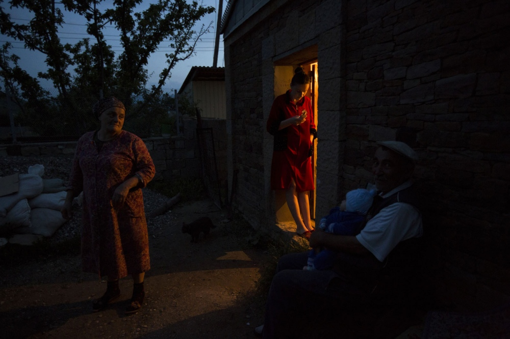A local lady stands on her cell phone in the light of a shop doorway in the village of Chokh.