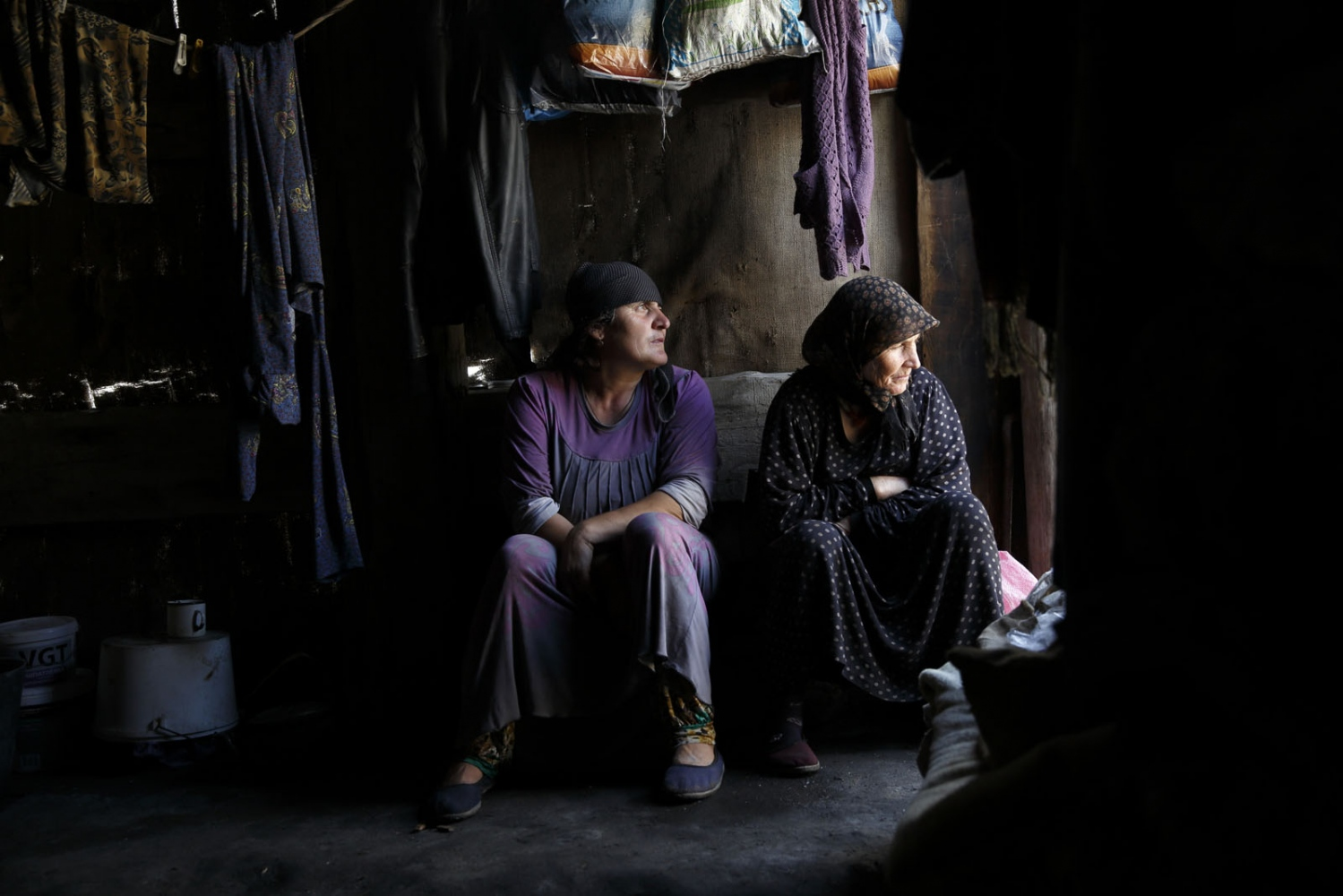 Women from one of the last remaining salt making family from Kvankhidatli village sit inside a hut where they cook the salt whilst it rains outside.