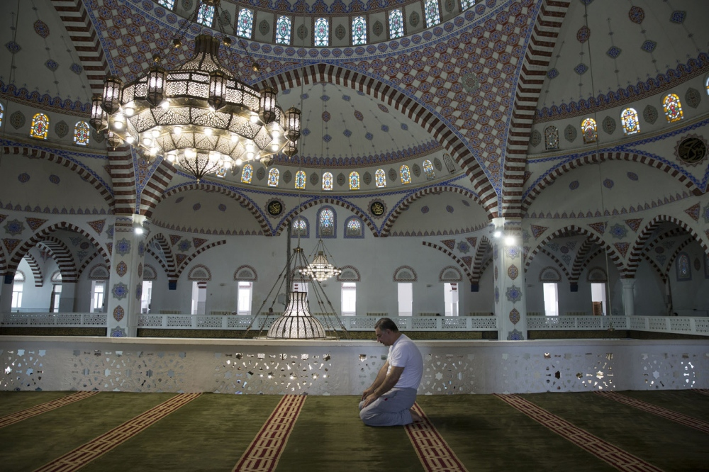A Muslim man prays during Ramadan inside The Grand Mosque in Makhachkala. It is the main mosque of the Republic of Dagestan and is supposed to have been designed after the Sultan Ahmed Mosque in Istanbul. The mosque was completed and consecrated in 1998 and can accommodate 17,000 worshippers.