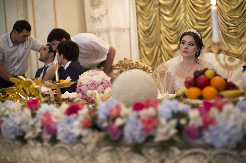 A bride and groom sit on an elaborate stage during a glamorous ceremony in an expensive wedding hall in Makhachkala.